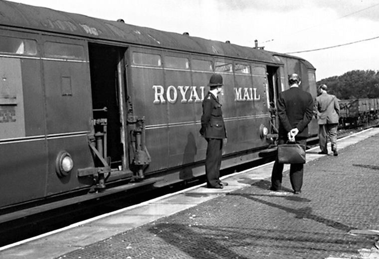 A 1960s Royal Mail train with policeman and businessman standing outside