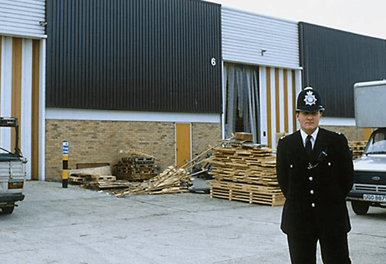 1980s policeman standing outside an industrial building