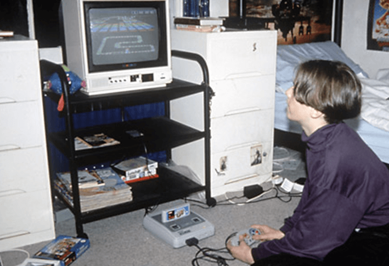 A boy in his bedroom playing Chrono Trigger on a Super Nintendo