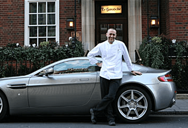 Michel Roux posing outside his restaurant Le Gavroche with a sports car