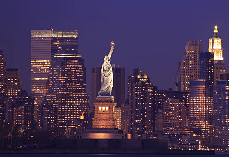The Statue of Liberty lit up at night with a New York skyline backdrop