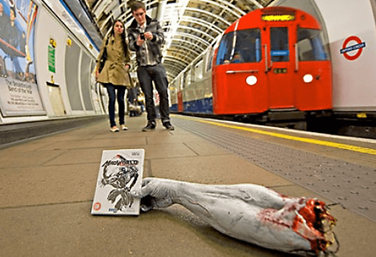 A severed arm holding a computer game on the Underground