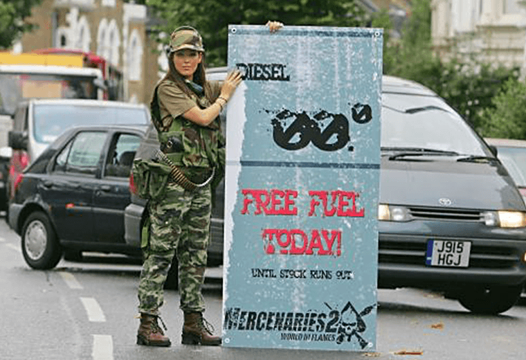 Military girl holding free fuel sign for Mercenaries 2: World in Flames publicity stunt