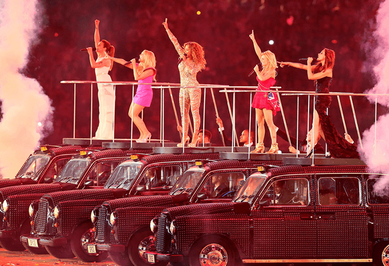 The Spice Girls performing on top of black cabs