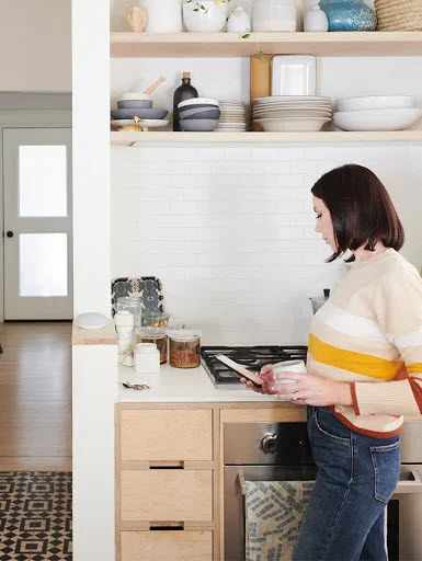 Woman in kitchen, holding coffee mug. Nest Mini in background on countertop.